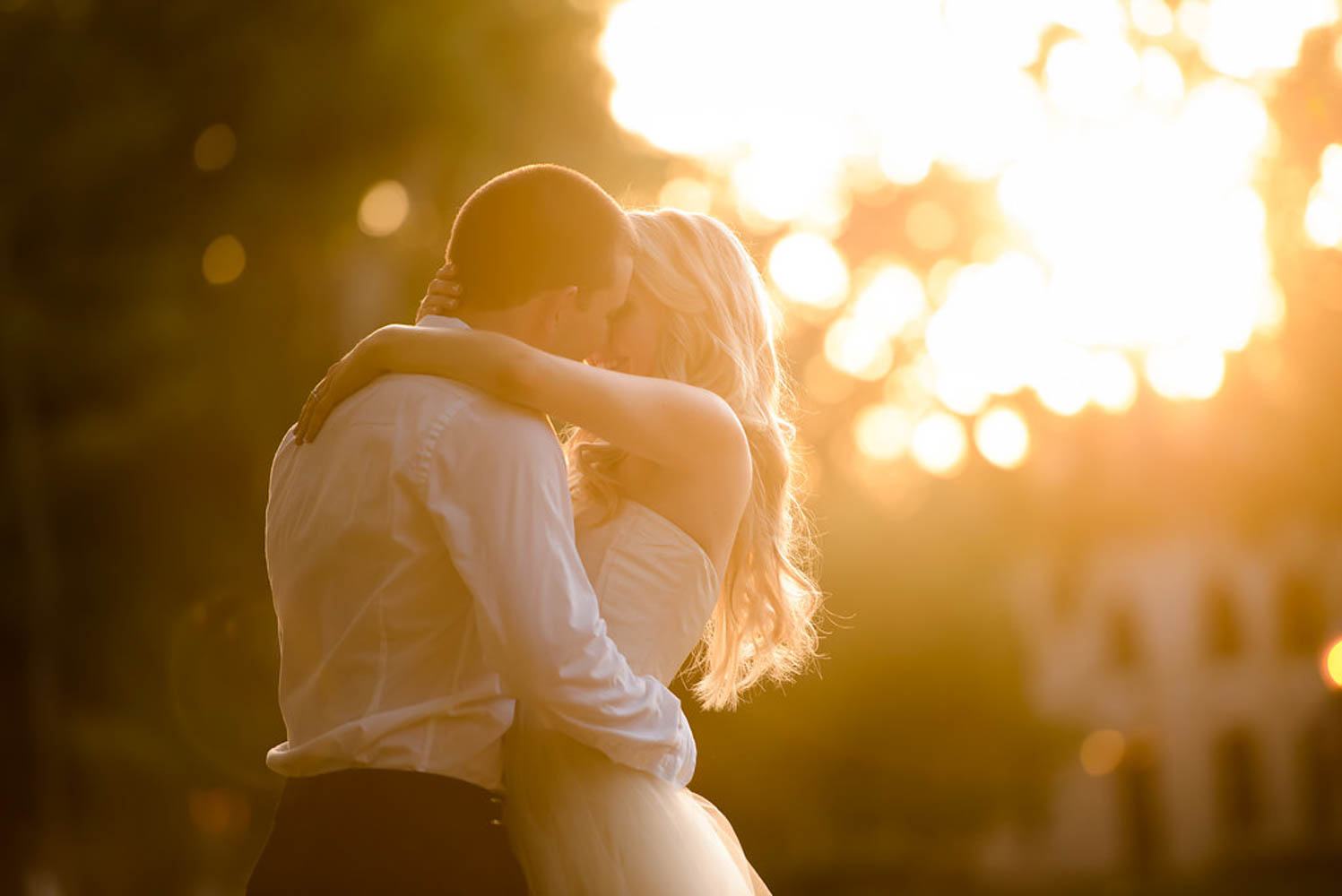 couple hugging with sunflare behind them