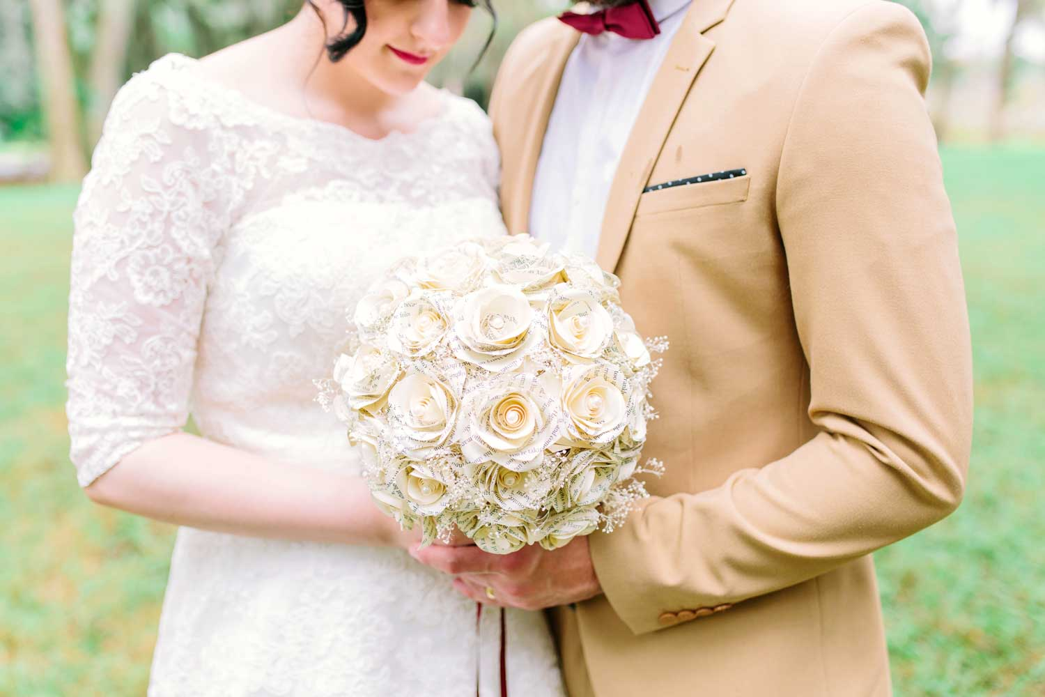 bride and groom holding paper flower bridal bouquet