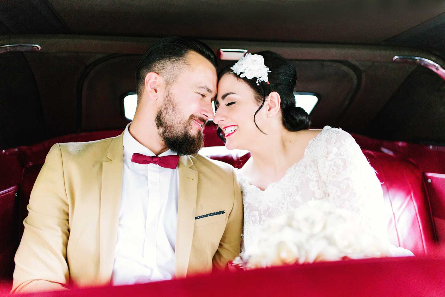 couple sitting in the back seat of a vintage car on their wedding day