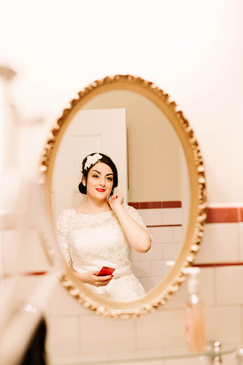 bride smiling looking into vintage mirror