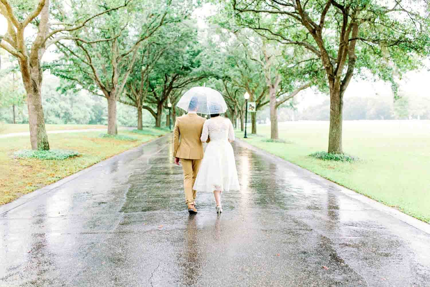 bride and groom walking under a clear umbrella at Cypress Grove Park