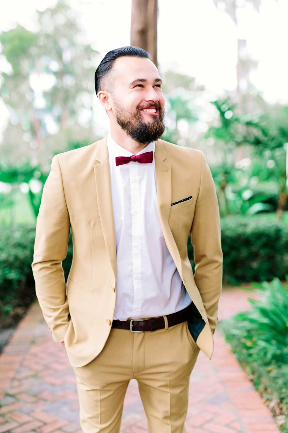 groom in burgundy bowtie and khaki suit smiling