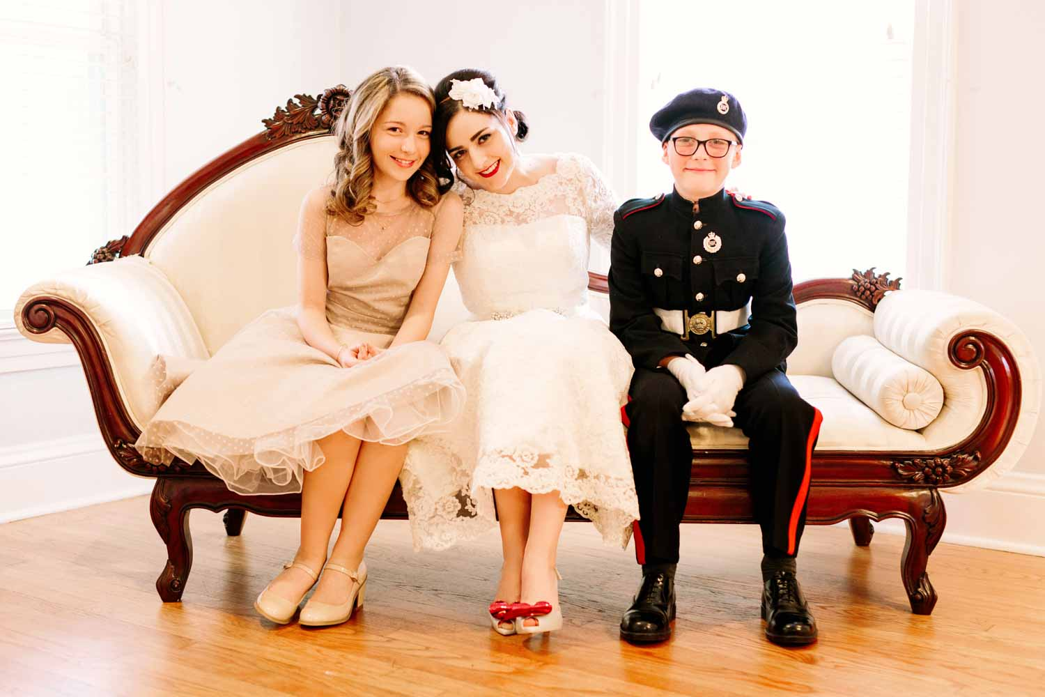 bride sitting on vintage couch with flower girl and ring bearer