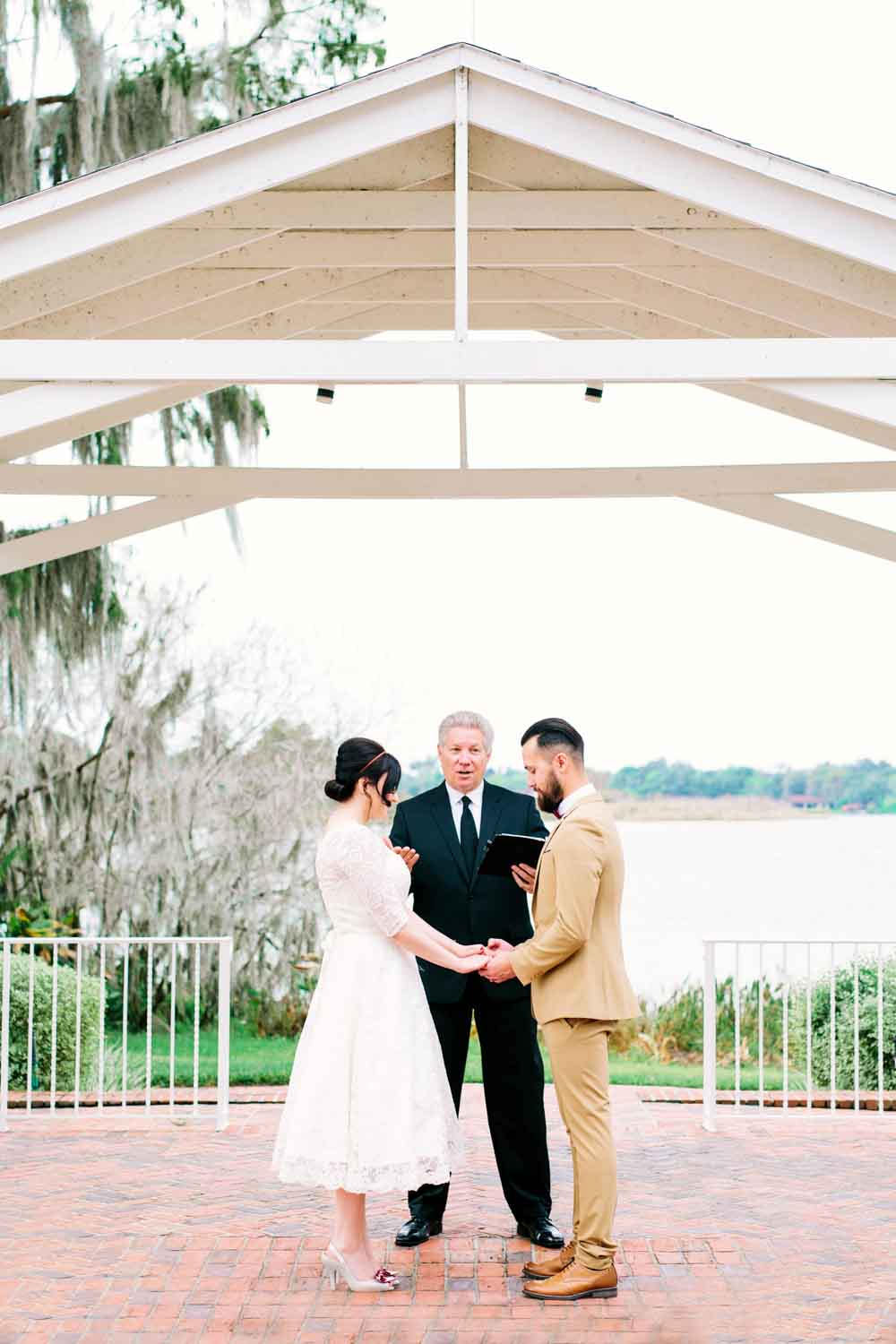 couple holding hands saying wedding vows