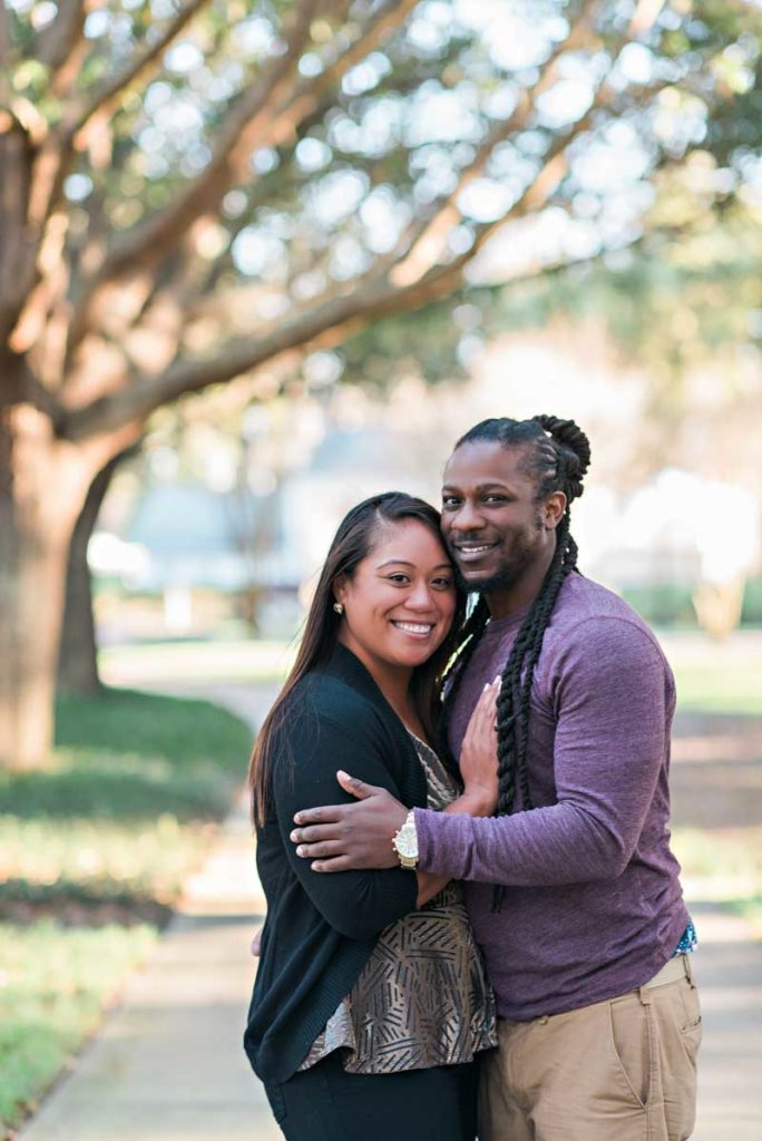 couple smiling under tree for photo