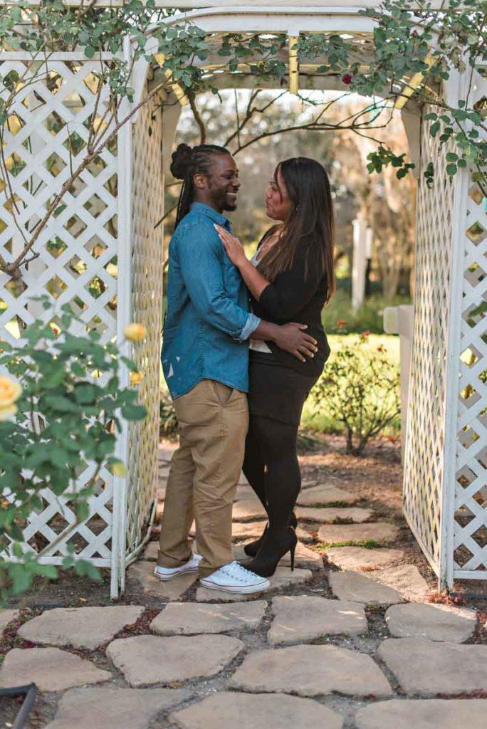 couple smiling under white pergola at Cypress Grove park