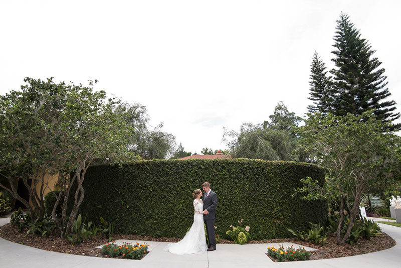 bride and groom standing in front of hedge wall at the Capen House