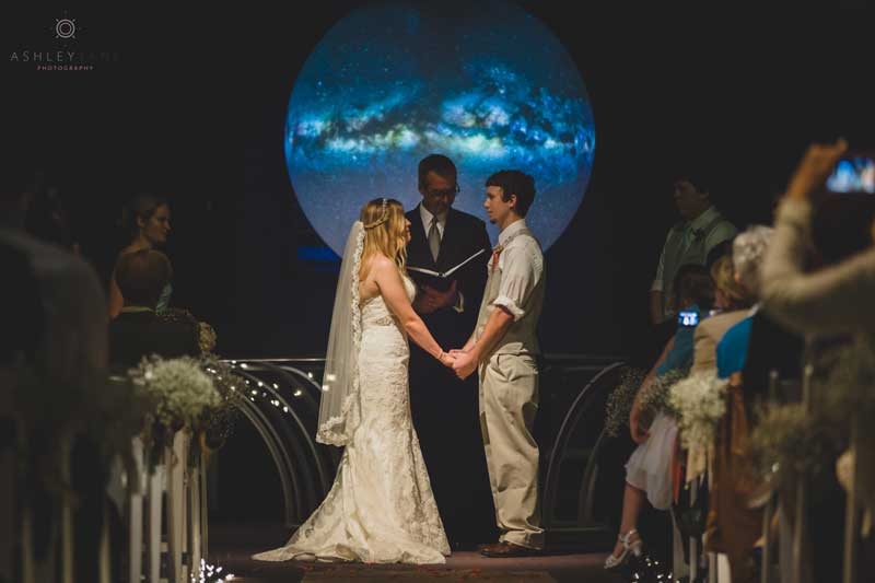 couple standing in front of planet for wedding ceremony at the Orlando Science Center
