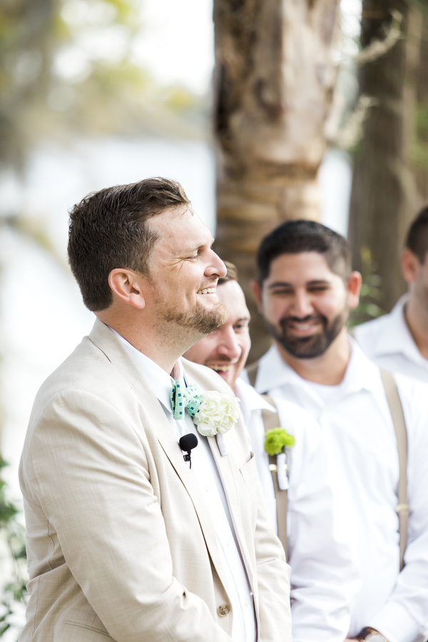 groom smiling while bride walks up the aisle
