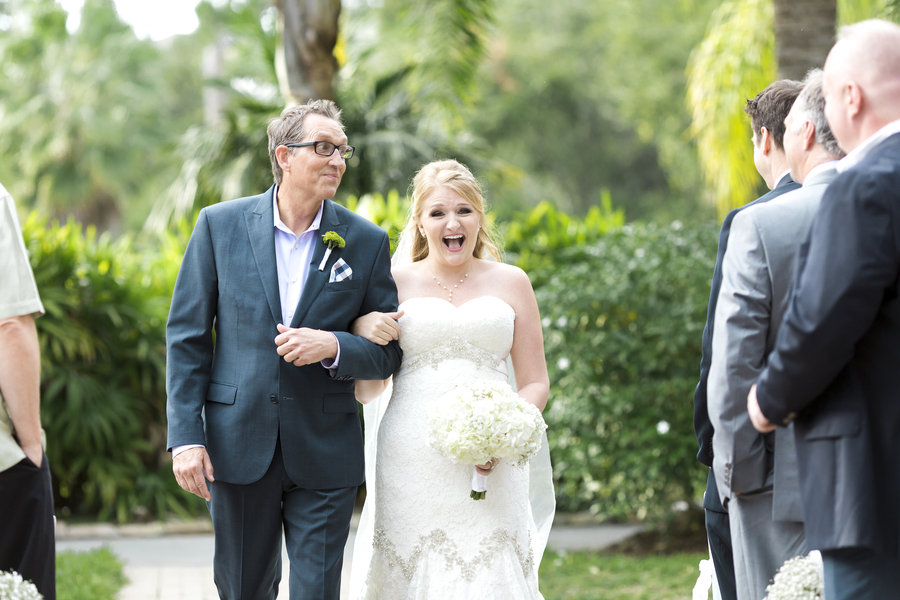 bride laughing while walking up the aisle with her dad