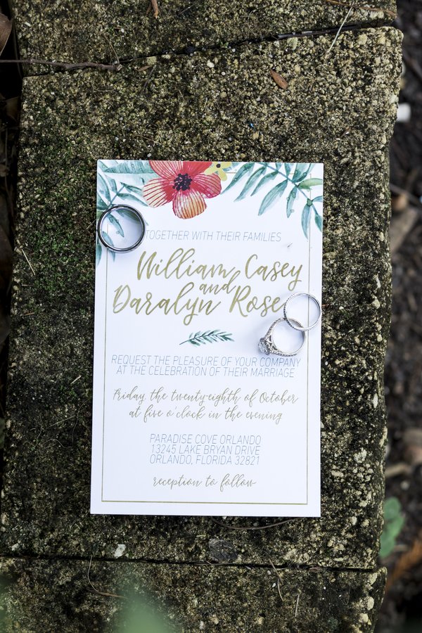tropical wedding invitation with wedding rings on top