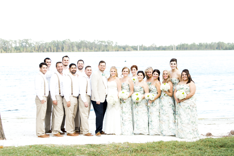 wedding party posing for photo on a lakefront beach