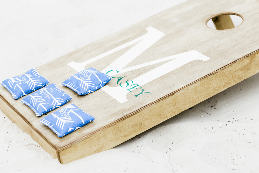 custom wedding cornhole board with blue bags on them
