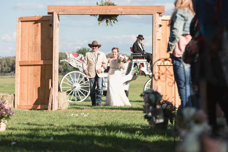 brides walking with father through rustic doors for outdoor wedding