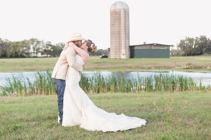 bride and groom kissing in front of pond and silo