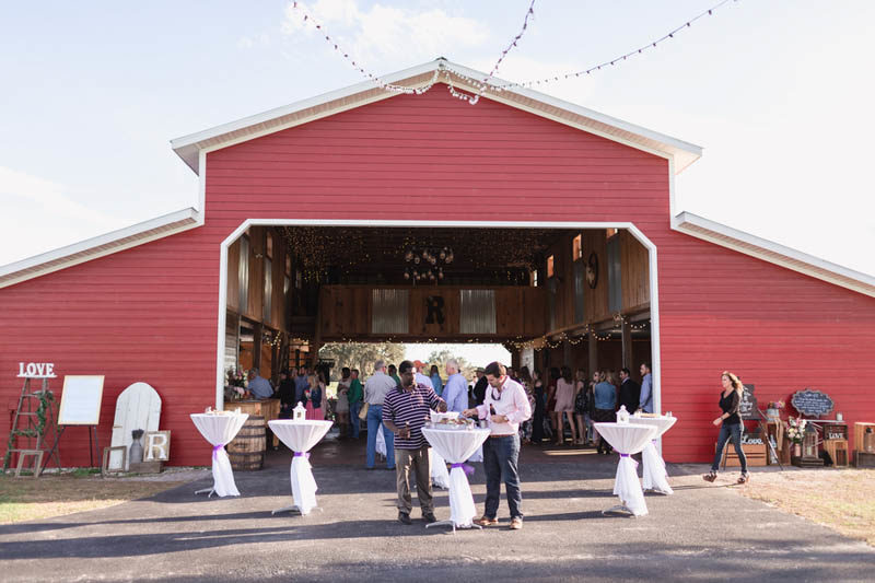wedding cocktail hour in front of a red barn