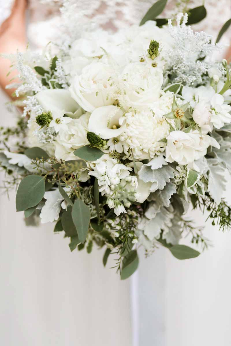 bride holding white and green bouquet