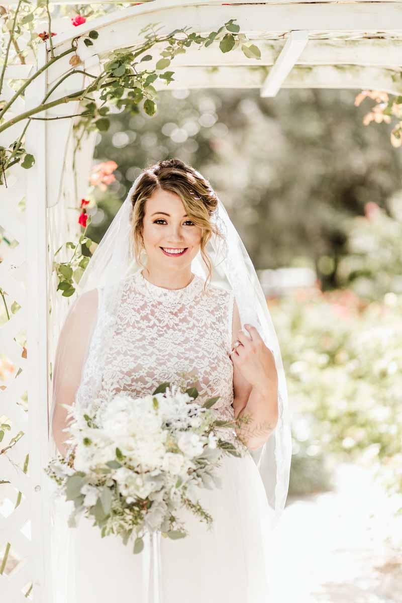bride standing under vine pergola