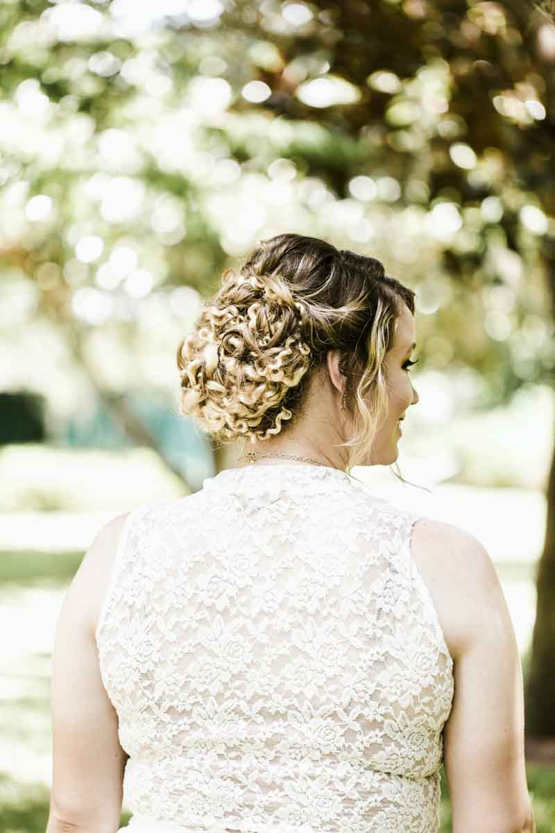 bride in lace dress with curly updo