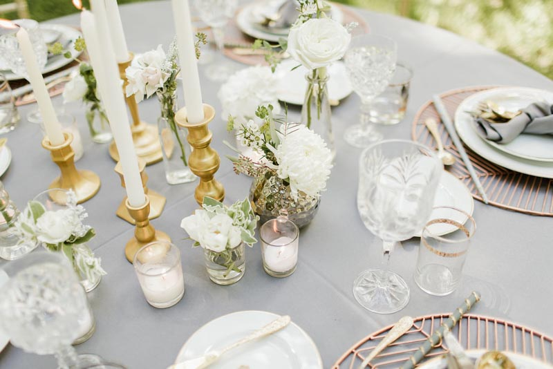 brass candlesticks and glass bottles on reception table