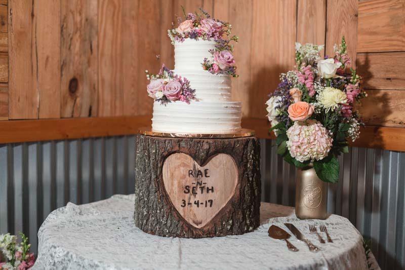 white wedding cake on wood stumo