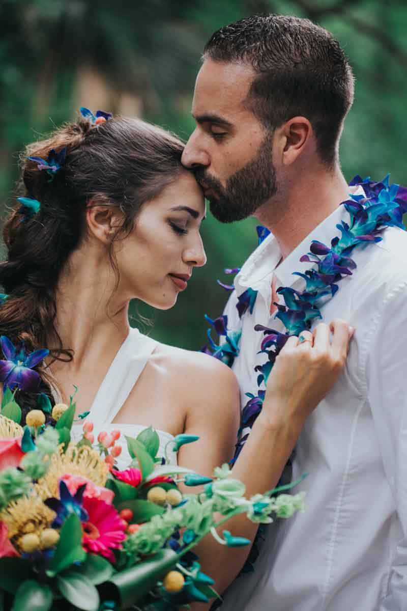 groom kissing forehead of bride hold bouquet