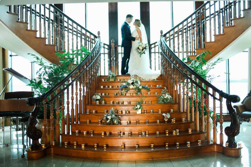 couple on staircase with floral arrangements on the steps