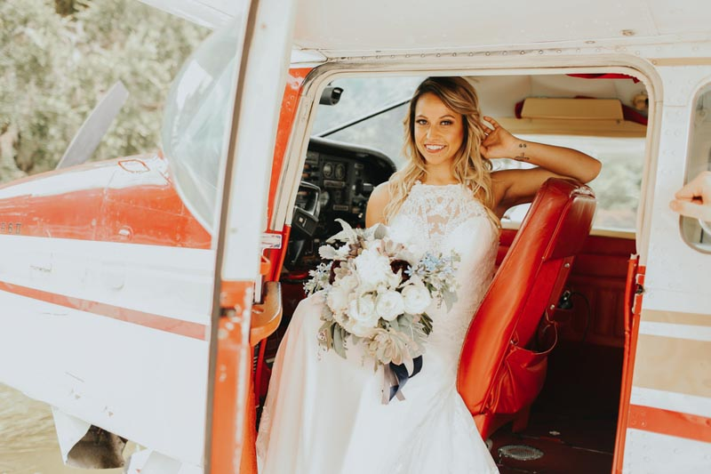 bride holding bouquet sitting in the cockpit of a seaplane