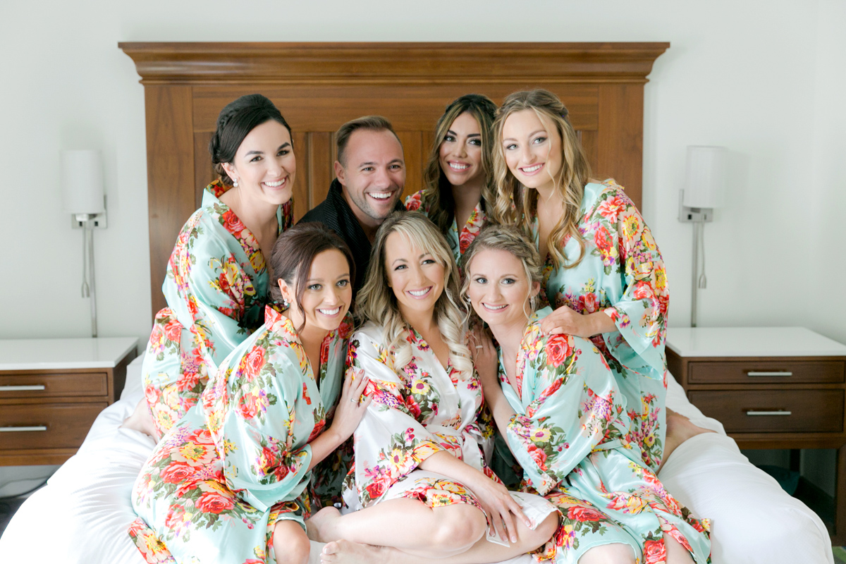 bride with bridesmaids in floral robes on bed