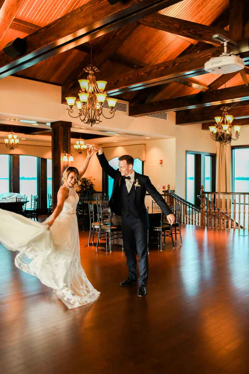 groom twirling bride in reception space