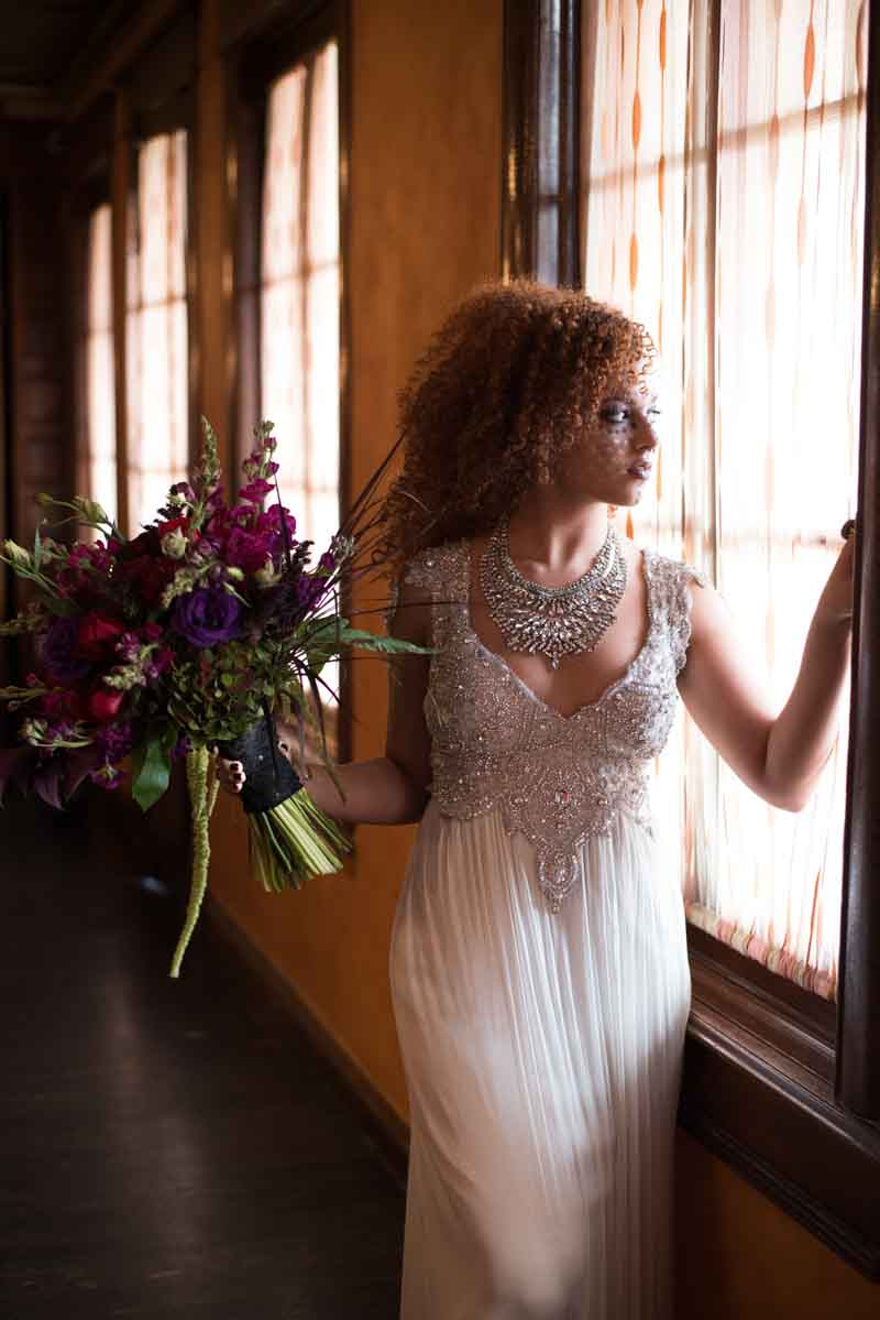 bride wearing beading wedding gown looking out window