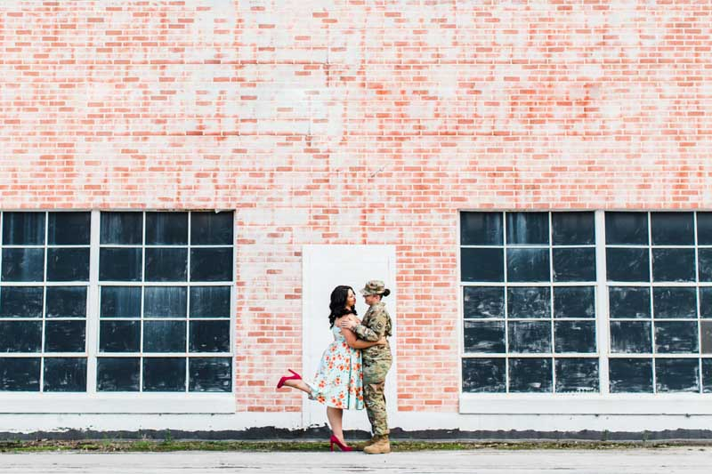 couple standing in front of brick wall