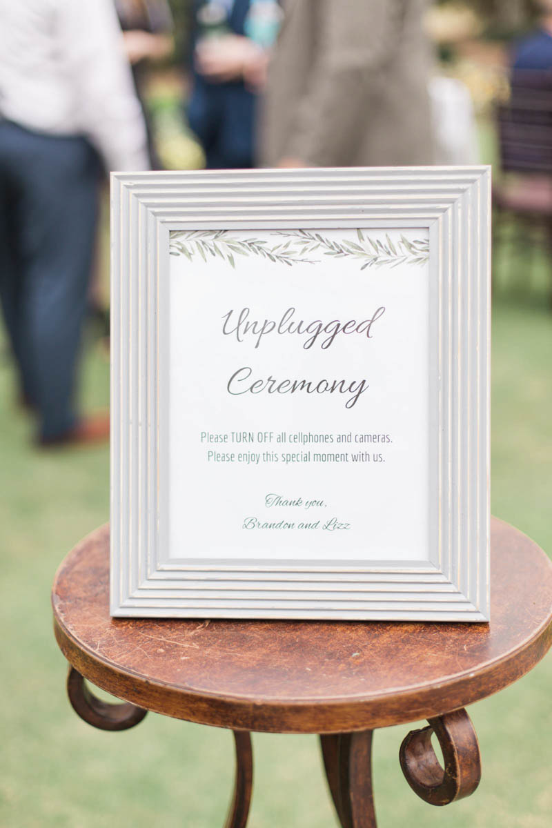 Grey framed unplugged wedding ceremony sign on table