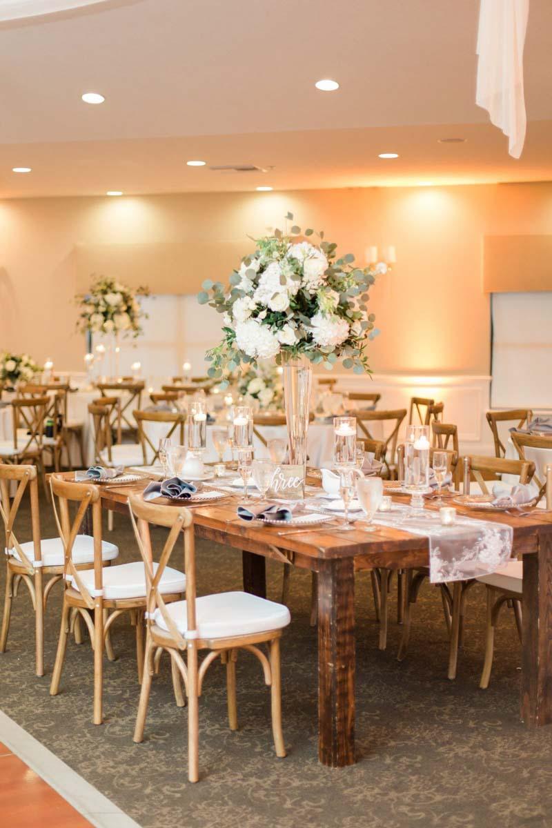 tall white wedding centerpiece on farm table