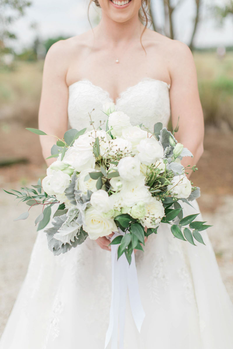 bride holding lush white and green bridal bouquet