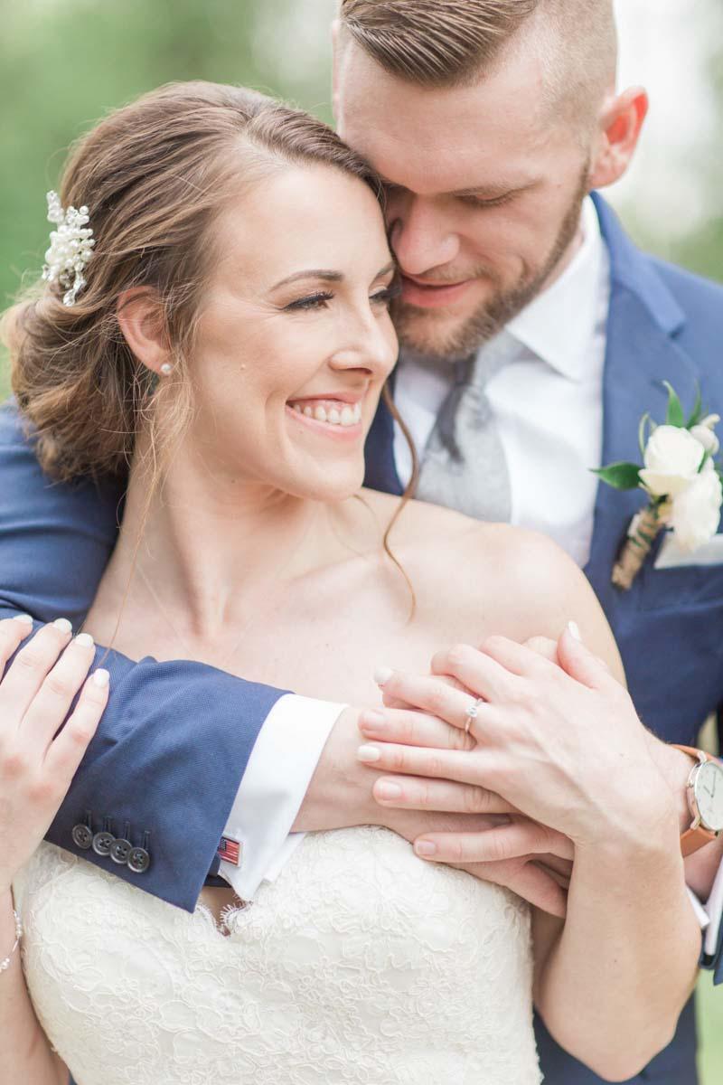 groom in blue suit hugging bride