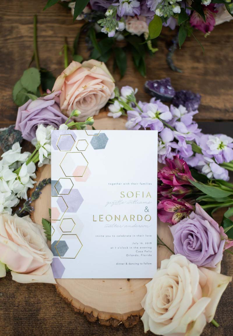 Geometric lavender and gold wedding invitations on flowers