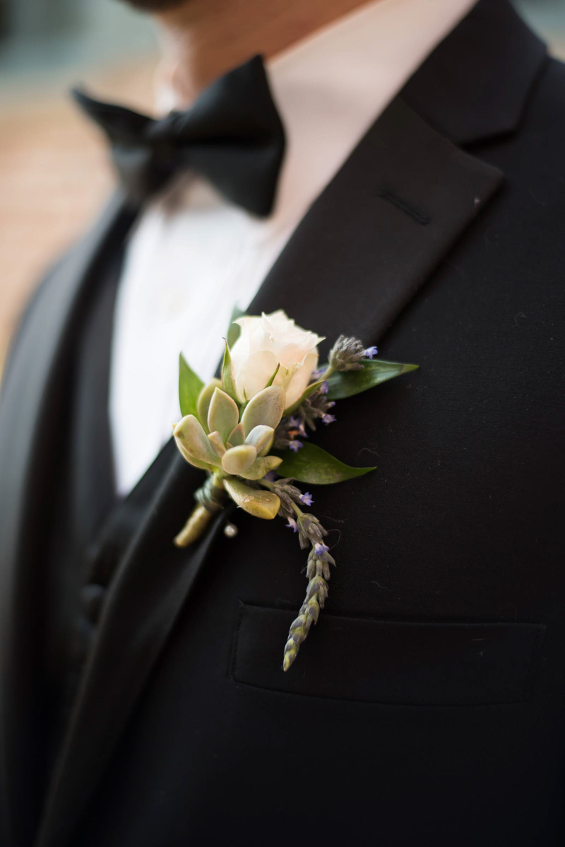 white rose and succulent boutonniere on black suit jacket
