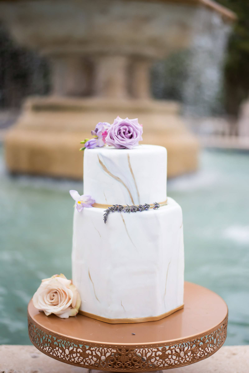 silver and gold marbled wedding cake with purple roses on top