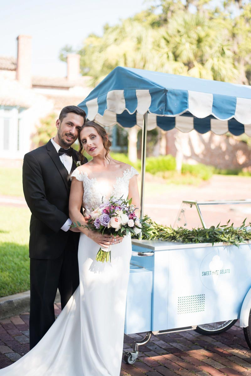 bride and groom smiling next to Sweet City Gelato cart