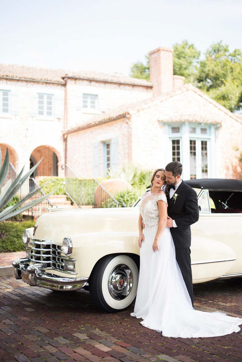 couple in wedding attire next to vintage car at Casa Feliz