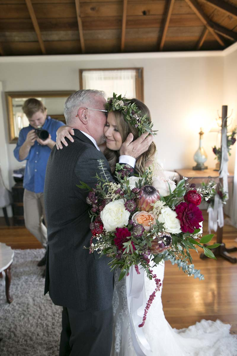 father of the bride hugging her on her wedding day