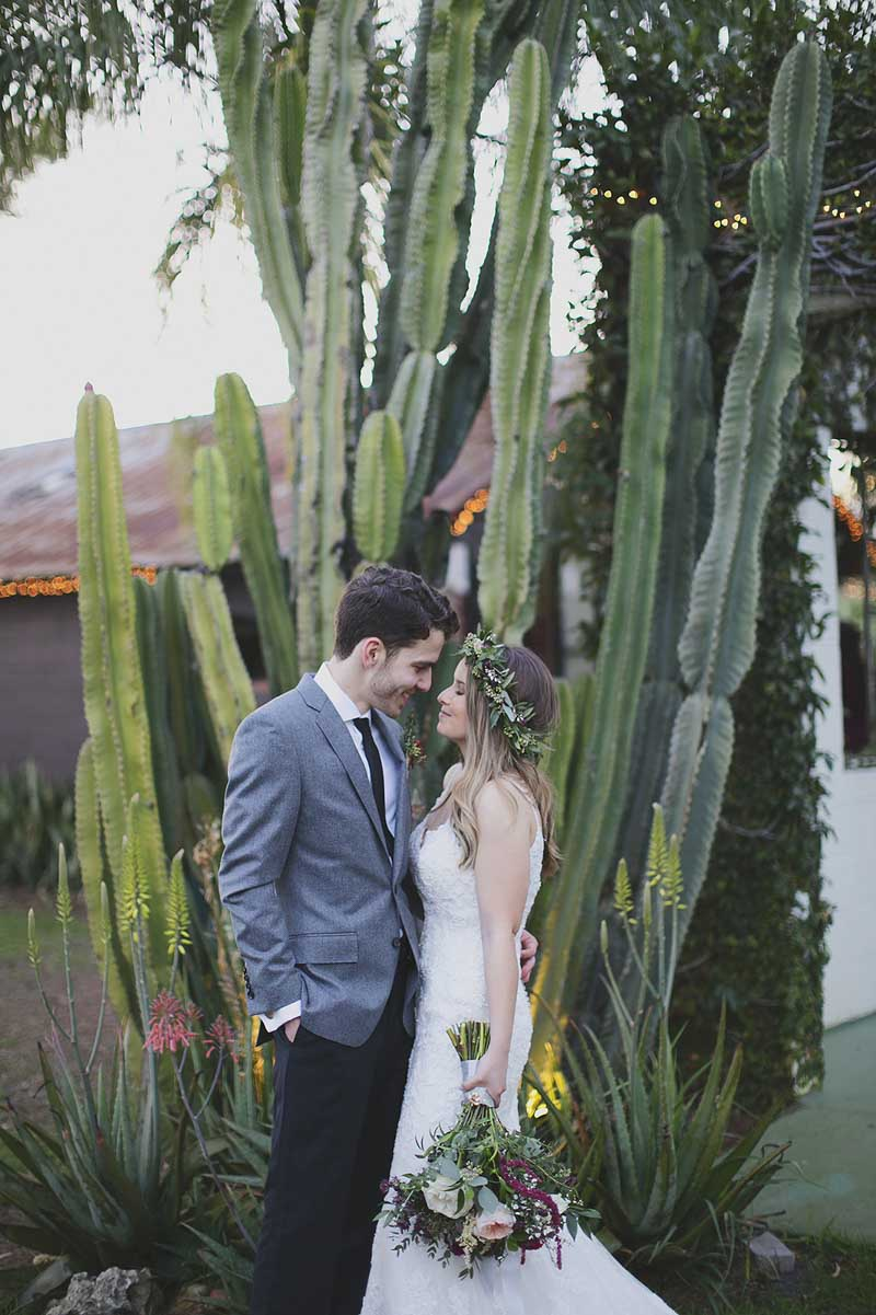 couple standing in front of a cactus on wedding day at The Acre Orlando