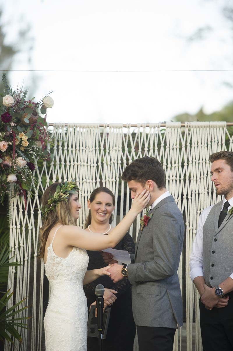 bride wiping away groom's tears at wedding alter