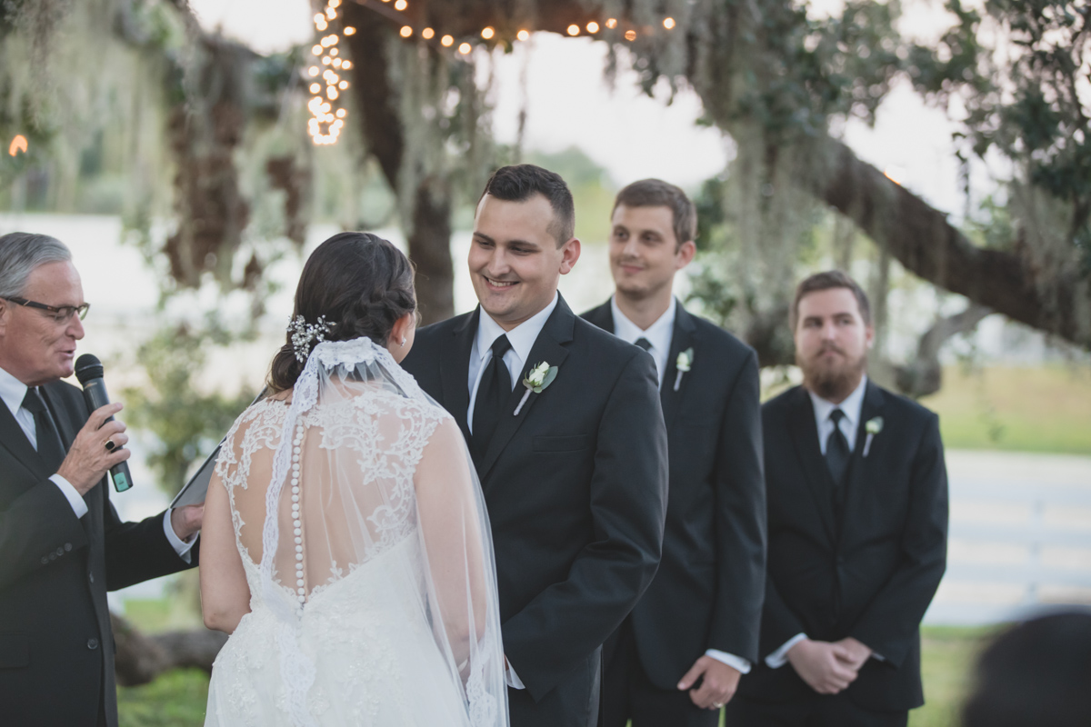 groom smiling at bride under oak tree for wedding ceremony