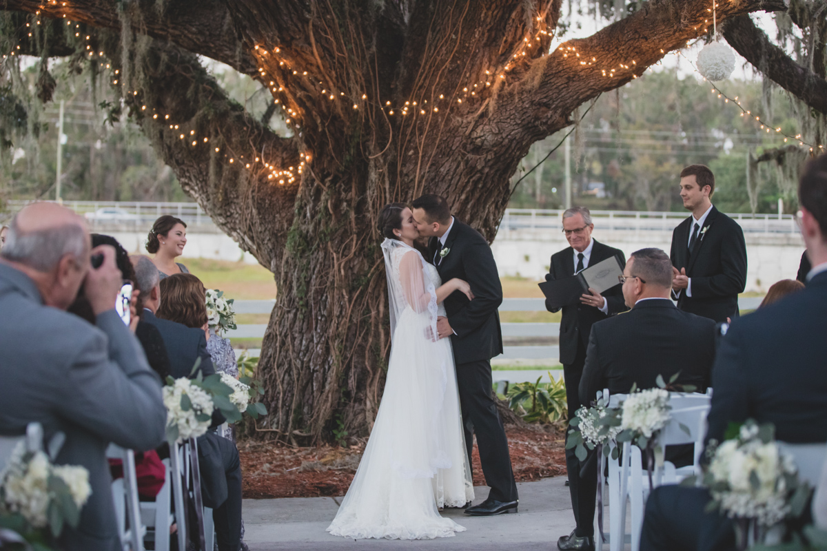 bride and groom's first kiss during wedding ceremony at Highland Manor