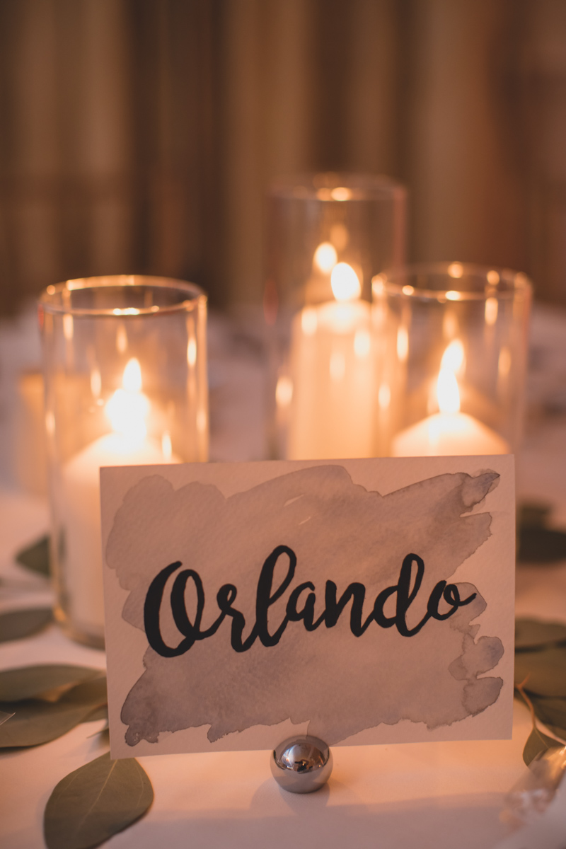Orlando table number in front of candles in glass cylinders