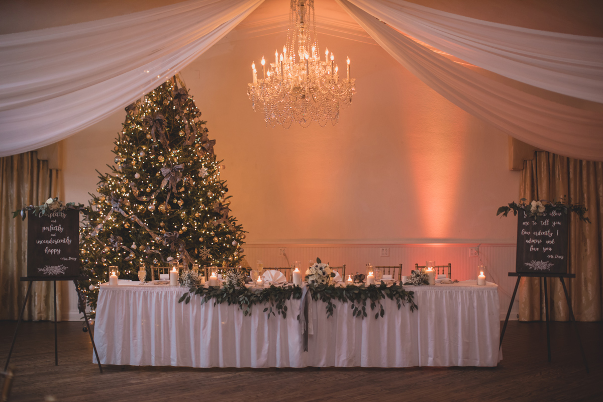 wedding party table in front of light Christmas tree