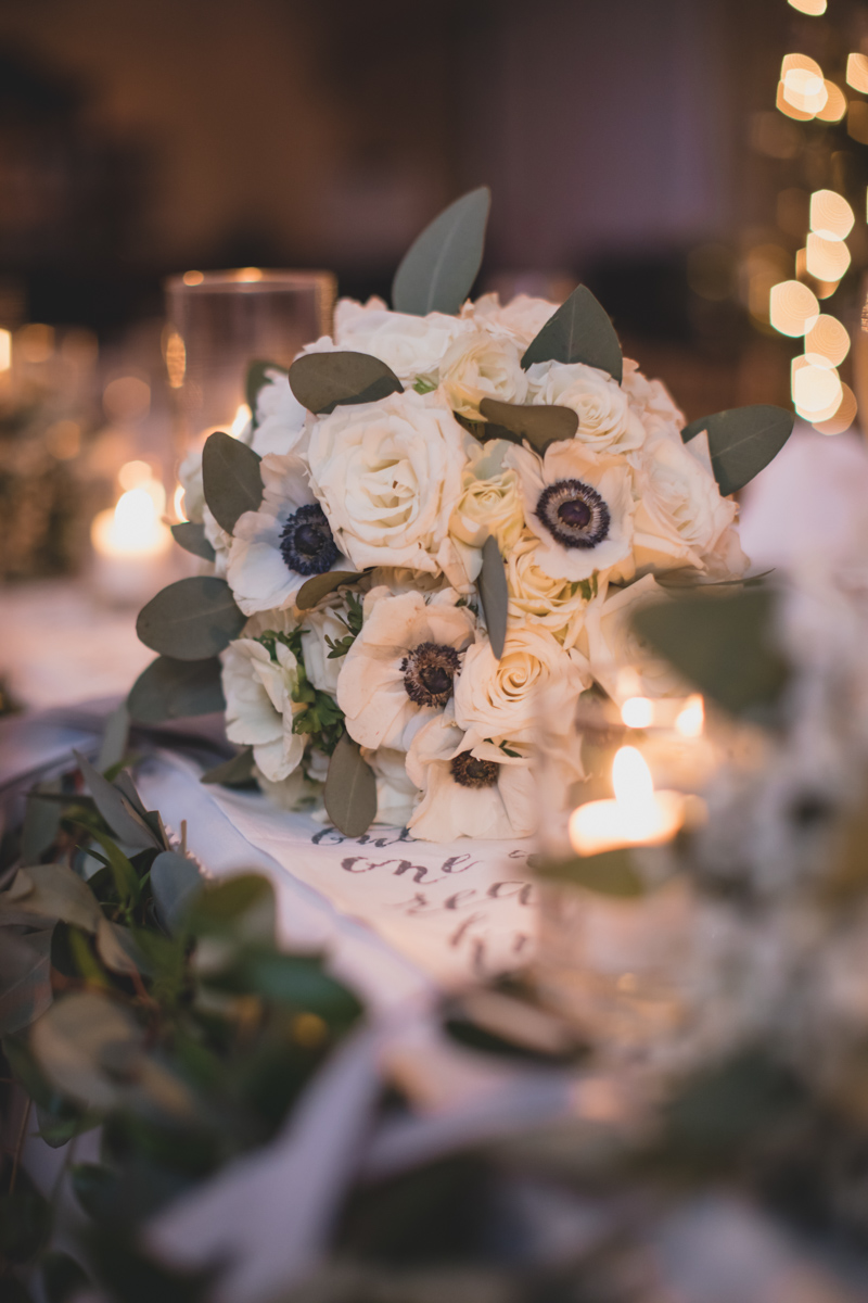 white bridal bouquet with white anemonies and roses on table