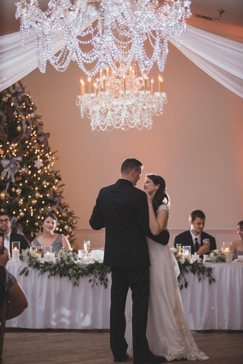 bride and groom dancing under crystal chandelier at wedding
